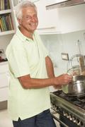 Senior Man Preparing Meal At Cooker Stock Photos