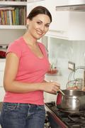 Woman Preparing Meal At Cooker Stock Photos