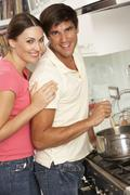 Couple Preparing Meal At Cooker Stock Photos