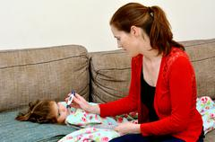 Caring mother taking care of her ill girl child - stock photo