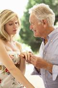 Older Man Proposing To Younger Woman Stock Photos