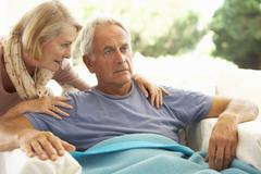 Wife Comforting Senior Man Feeling Unwell Resting Under Blanket Stock Photos