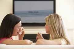 Two Women Watching Sad Movie On Widescreen TV At Home - stock photo