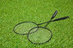 Crossed badminton rackets lying on grass - stock photo