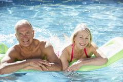 Senior Couple Relaxing In Swimming Pool On Airbed Together - stock photo