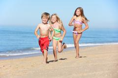 Children Running Along Summer Beach Stock Photos