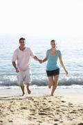 Young Couple Running Along Beach On Holiday - stock photo
