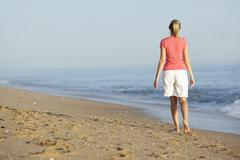 Woman Walking Along Beach - stock photo