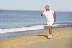 Senior Man Jogging Along Beach - stock photo