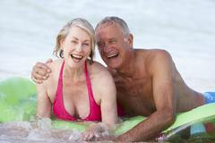 Senior Couple Having Fun In Sea On Airbed Stock Photos