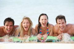 Group Of Friends Having Fun In Sea On Airbed - stock photo