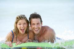 Young Couple Having Fun In Sea On Airbed - stock photo