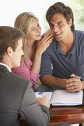 Couple Meeting With Financial Advisor At Home - stock photo