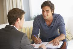 Man Meeting With Financial Advisor At Home Stock Photos