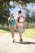 Middle Aged Couple Hiking Through Countryside Viewed From Behind Stock Photos