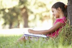 Young Girl Sketching In Countryside Leaning Against Tree Stock Photos