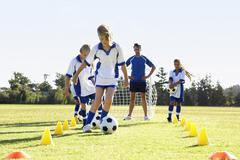 Group Of Children In Soccer Team Having Training With Coach Stock Photos