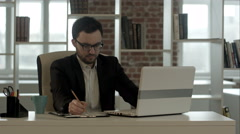 Young man with funny glasses working on his notebook, with a fresh cup of coffee Stock Footage