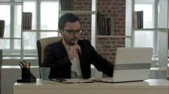 Businessman in funny glasses typing on keyboard has very good idea Stock Footage