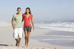 Young Couple Walking Along Beach - stock photo