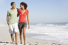Young Couple Walking Along Beach - stock photo