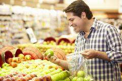 Man Shopping For Produce In Supermarket Stock Photos