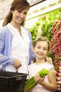 Mother And Daughteer Shopping For Produce In Supermarket - stock photo