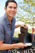 Hispanic Man Checking Mailbox - stock photo