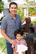 Hispanic Father And Son Checking Mailbox Stock Photos
