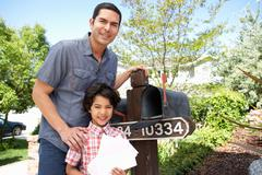 Hispanic Father And Son Checking Mailbox - stock photo