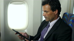 Businessman on plane with pad 2 Stock Footage