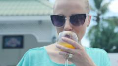 Woman drinking orange juice while walking in garden during sunny days. Stock Footage