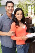 Hispanic Couple Checking Mailbox - stock photo