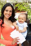 Hispanic Mother And Baby Checking Mailbox - stock photo
