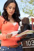 Worried Hispanic Woman Checking Mailbox - stock photo