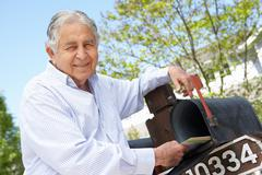 Senior Hispanic Man Checking Mailbox - stock photo