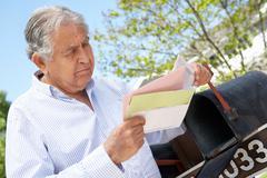 Worried Senior Hispanic Man Checking Mailbox - stock photo