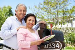 Senior Hispanic Couple Checking Mailbox - stock photo