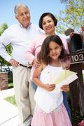Hispanic Grandparents And Granddaughter Checking Mailbox - stock photo