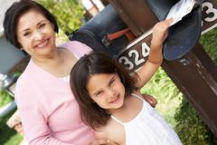 Hispanic Grandmother And Granddaughter Checking Mailbox - stock photo