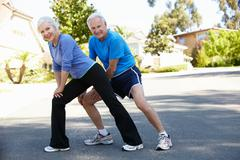 Elderly man and younger woman jogging - stock photo