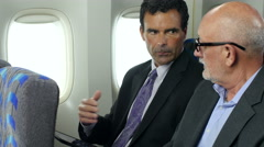 Businessmen on a plane looking at  ipad/tablet Stock Footage