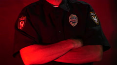 Close up of a police officer's chest, arms crossed, flashing lights Stock Footage