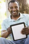 Senior African American Man In Park Using Tablet Computer - stock photo
