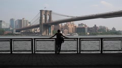 Woman Stands on New York Pier Looking at Brooklyn Bridge Stock Video Stock Footage