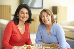 Hispanic Mother With Adult Daughter Enjoying Meal At Home - stock photo