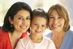 Portrait Of Hispanic Grandmother, Mother And Daughter Relaxing At Home Stock Photos
