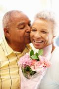 Senior man giving flowers to wife Stock Photos