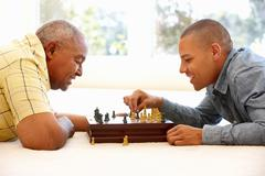 Senior man playing chess with son Stock Photos