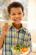 Young boy eating raw vegetables Stock Photos